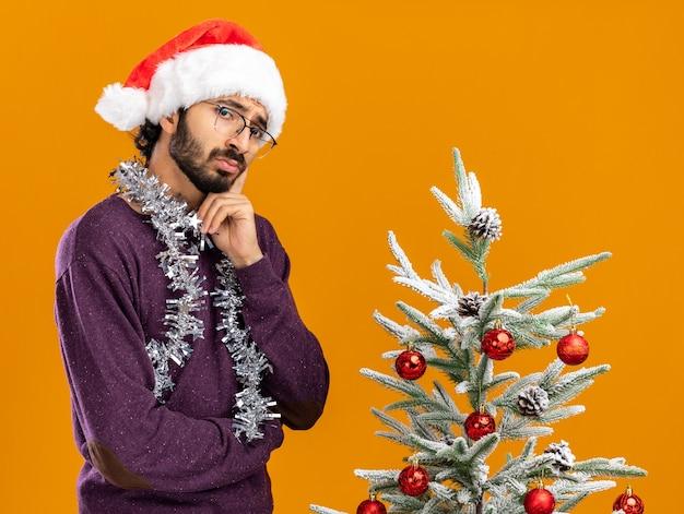 Penser un jeune beau mec debout à proximité d'un arbre de noël portant un chapeau de noël avec une guirlande sur le cou mettant le doigt sur la joue isolé sur un mur orange