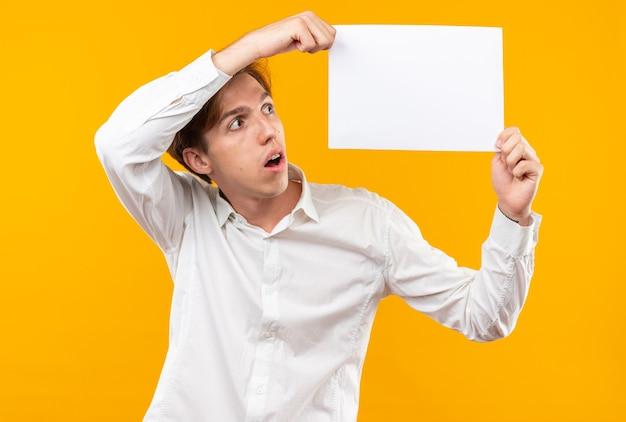 Penser un jeune beau mec portant une chemise blanche tenant et regardant du papier vierge isolé sur un mur orange