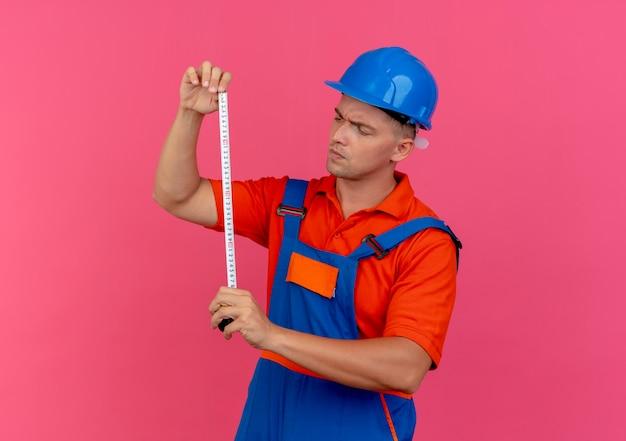 Penser jeune constructeur de sexe masculin portant l'uniforme et un casque de sécurité tenant et regardant un mètre ruban sur rose