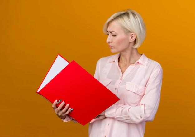 Penser jeune femme slave blonde tenant et regardant le dossier isolé sur le mur orange