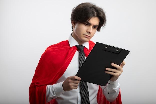 Penser jeune gars de super-héros portant une cravate tenant et regardant le presse-papiers isolé sur fond blanc