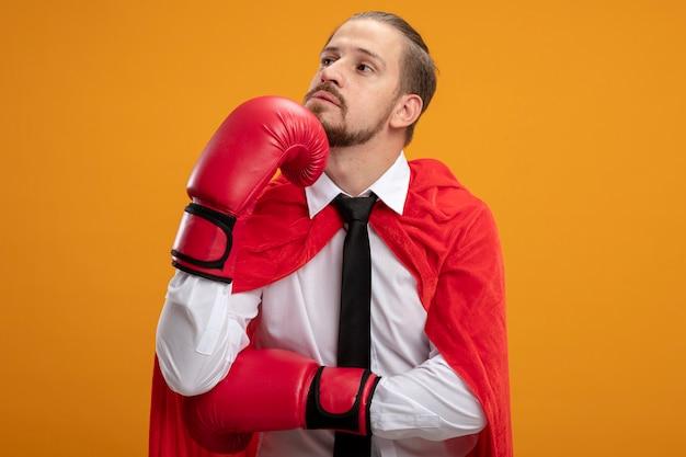 Penser jeune gars de super-héros regardant côté portant une cravate et des gants de boxe mettant la main sous le menton isolé sur fond orange