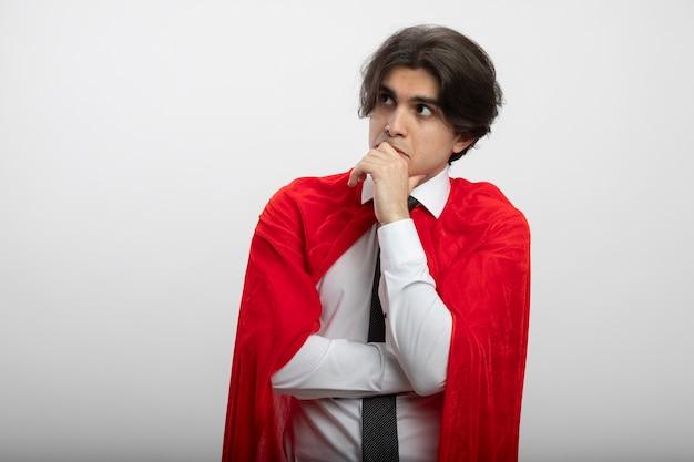 Penser jeune gars de super-héros regardant le côté portant une cravate mettant la main sur le menton isolé sur fond blanc