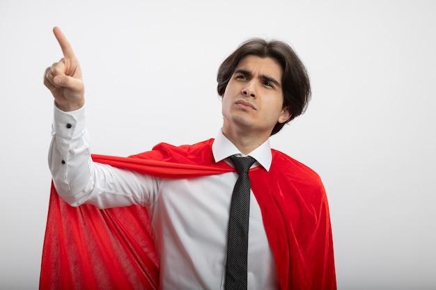 Penser jeune gars de super-héros regardant le côté portant des points de cravate sur le côté isolé sur fond blanc