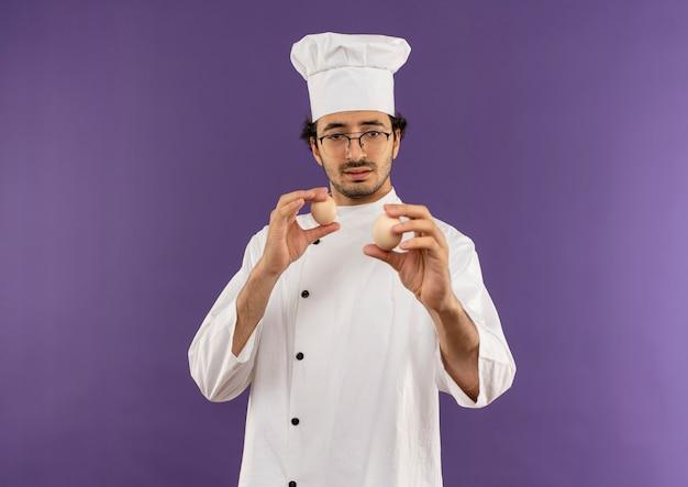 Penser jeune homme cuisinier portant l'uniforme de chef et des lunettes tenant et regardant des œufs sur violet