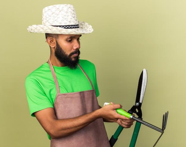 Penser un jeune jardinier afro-américain portant un chapeau de jardinage tenant et regardant des tondeuses avec un râteau de houe isolé sur un mur vert olive