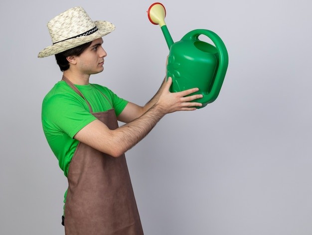 Penser jeune jardinier mâle en uniforme portant chapeau de jardinage tenant et regardant arrosoir