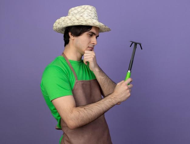 Penser jeune jardinier mâle en uniforme portant chapeau de jardinage tenant et regardant houe râteau a attrapé le menton