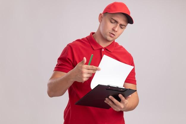 Penser jeune livreur en uniforme avec capuchon feuilletant le presse-papiers isolé sur mur blanc