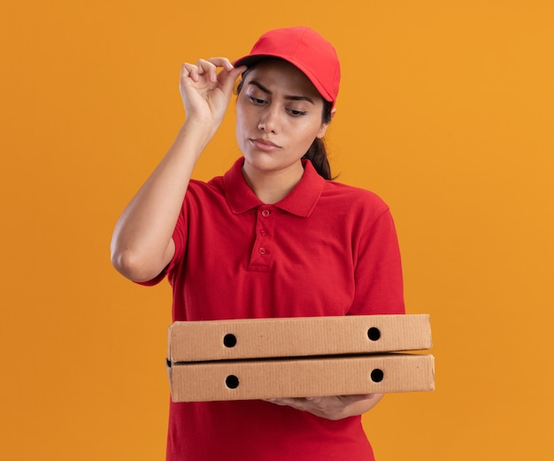 Penser jeune livreuse en uniforme et cap tenant et regardant les boîtes de pizza holding cap isolé sur mur orange