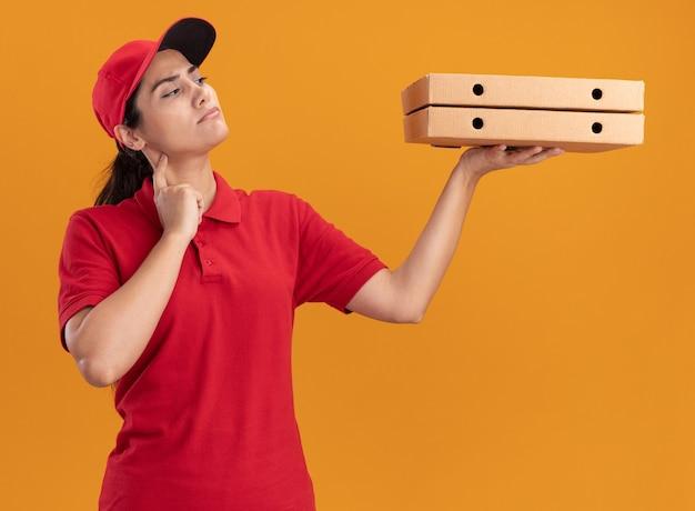 Penser jeune livreuse en uniforme et cap tenant et regardant des boîtes de pizza isolé sur mur orange