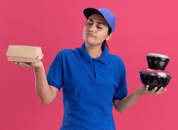Penser jeune livreuse en uniforme avec capuchon tenant et regardant les contenants de nourriture isolés sur mur rose