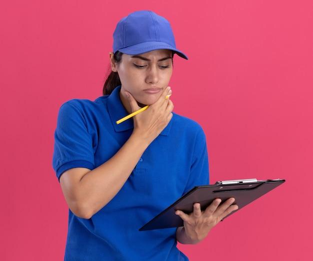 Penser une jeune livreuse en uniforme avec une casquette tenant et regardant le presse-papiers saisi le menton isolé sur un mur rose