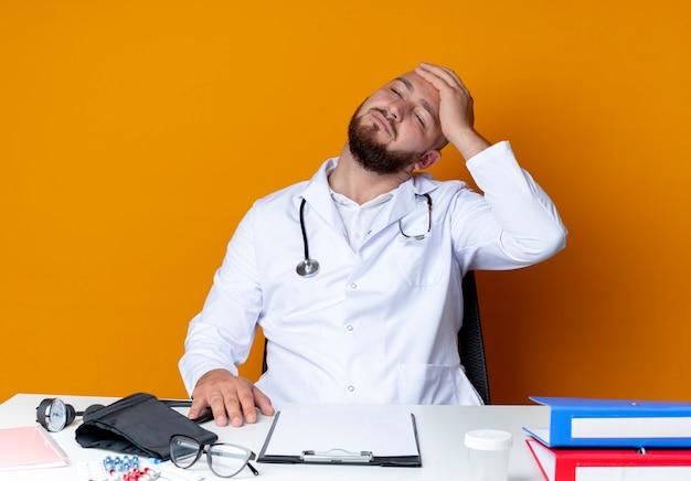 Penser jeune médecin de sexe masculin chauve portant une robe médicale et un stéthoscope assis au bureau de travail avec des outils médicaux mettant la main sur la tête isolée sur un mur orange