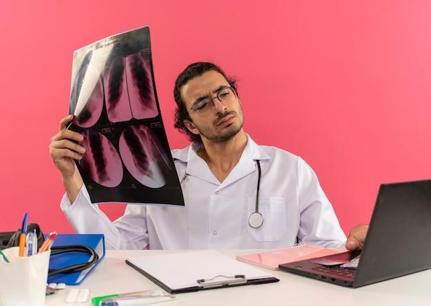 Penser un jeune médecin de sexe masculin avec des lunettes médicales portant une robe médicale avec un stéthoscope assis au bureau
