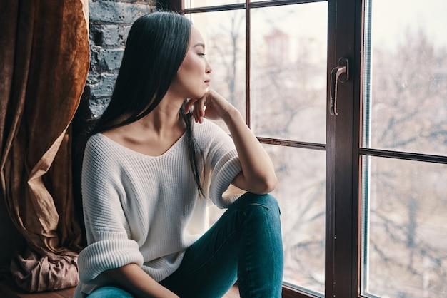 Penser à.... jolie jeune femme gardant la main sur le menton et regardant ailleurs alors qu'elle était assise sur le rebord de la fenêtre à la maison