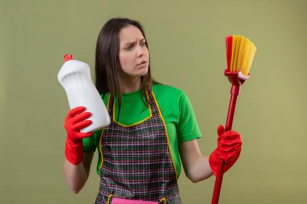 Penser le nettoyage de jeune fille en uniforme dans des gants rouges tenant un agent de nettoyage à la vadrouille sur sa main sur un mur vert isolé