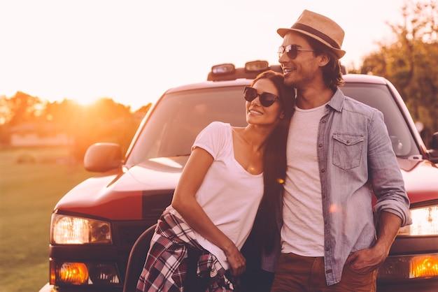Penser à un nouvel endroit où aller. beau jeune couple souriant à la réflexion tout en se liant les uns aux autres et en se penchant sur leur camionnette