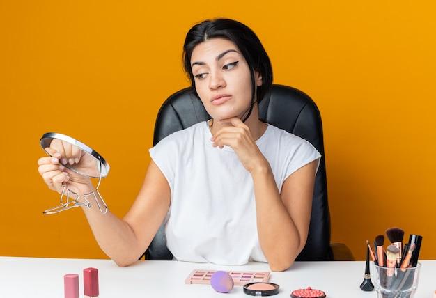 Penser qu'une belle femme est assise à table avec des outils de maquillage tenant et regardant un miroir mettant la main sur le menton
