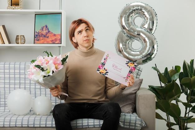 Penser à la recherche d'un beau mec le jour de la femme heureuse tenant un bouquet avec une carte de voeux assis sur un canapé dans le salon