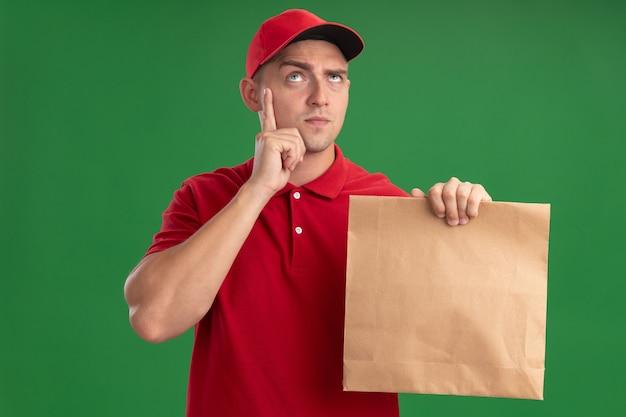 Penser à la recherche de jeune homme de livraison portant l'uniforme et le chapeau tenant le paquet de nourriture de papier mettant le doigt sur la joue isolé sur le mur vert