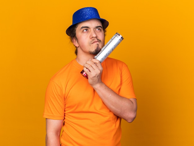 Penser à la recherche d'un jeune homme portant un chapeau de fête tenant un canon à confettis isolé sur un mur orange