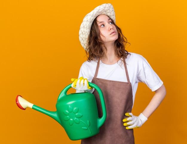 Penser à la recherche d'une jeune jardinière portant un chapeau de jardinage et des gants tenant un arrosoir mettant la main sur la hanche isolée sur un mur orange