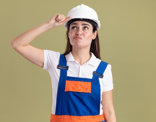 Penser en regardant côté jeune femme constructeur en uniforme isolé sur mur vert olive