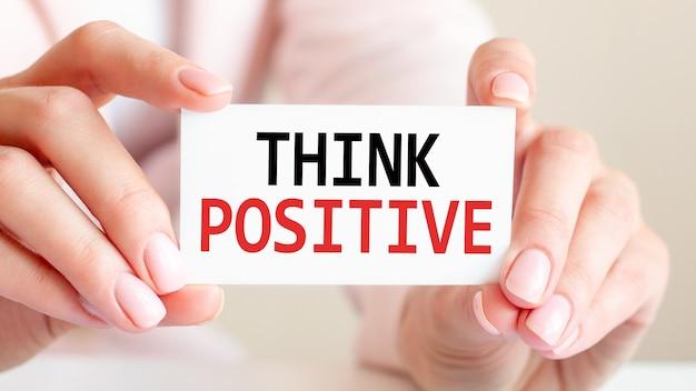 Pensez positif est écrit sur une carte de visite blanche entre les mains d'une femme