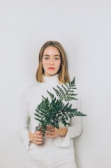 Pensif, femme, debout, fougère, feuilles