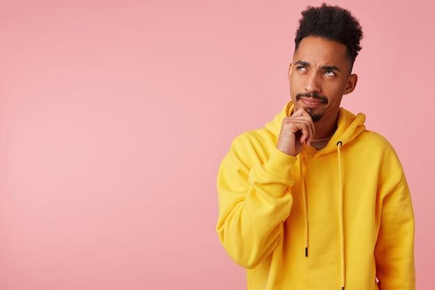 Pensif jeune homme à la peau sombre avec barbe tenant le menton avec la main levée et regardant vers le haut avec un léger sourire, traçant quelque chose en se tenant debout en sweat-shirt jaune
