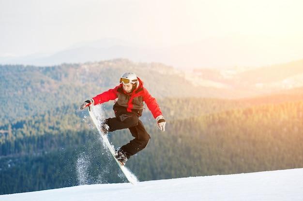 Pensionnaire homme sautant sur son snowboard
