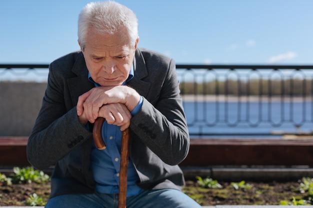 Un pensionné aux cheveux blancs intelligent et réfléchi se souvenant de sa femme et réfléchissant à son avenir alors qu'il était assis sur le banc