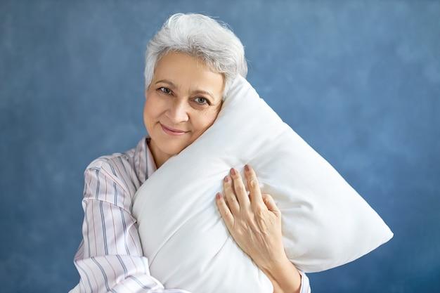 Pensionné posant et étreignant un oreiller doux blanc