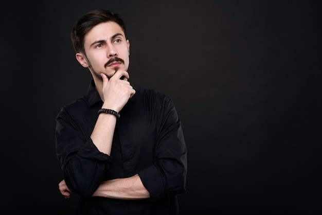 Pensive beau jeune homme en chemise noire touchant le menton tout en réfléchissant à l'idée