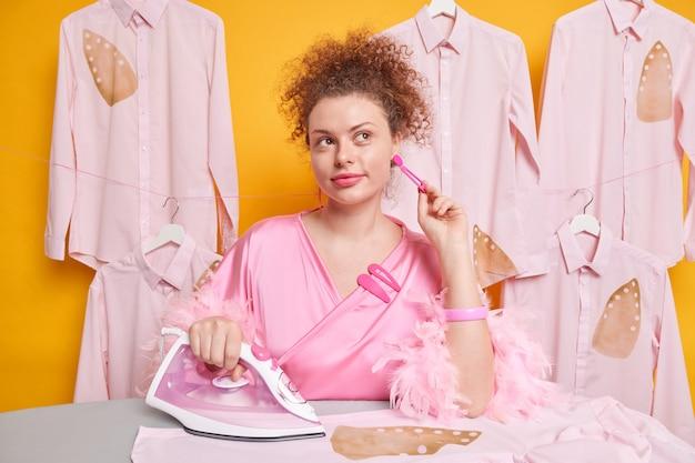 Pensive belle femme au foyer bouclée garde la main sur la boucle d'oreille regarde au loin avec une expression réfléchie utilise un fer électrique pour caresser des vêtements vêtus d'une robe domestique pose contre un mur jaune