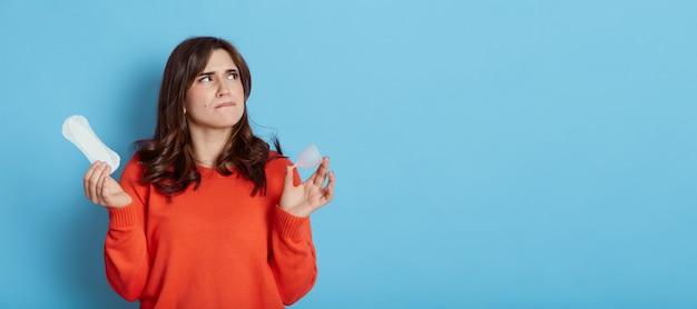 Pensive belle femme portant un pull orange décontracté à la recherche de suite avec une expression faciale réfléchie