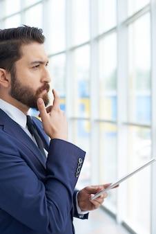 Pensive businessman regardant par la fenêtre