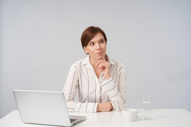 Pensive jeune belle femme aux cheveux bruns avec une coiffure décontractée à la recherche positive de côté et en penchant son menton sur la main levée, portant des vêtements formels tout en posant sur blanc