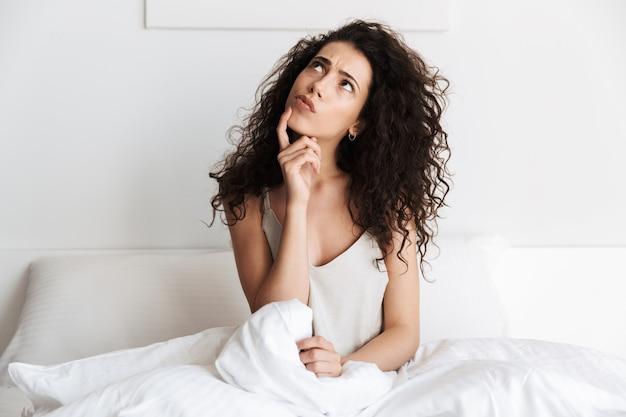 Pensive jeune femme aux cheveux bouclés foncés assis
