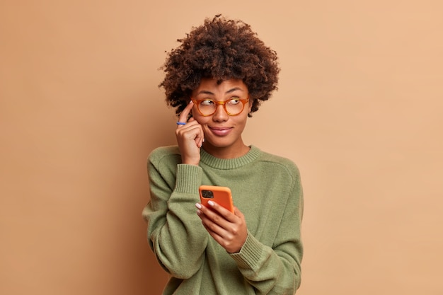 Pensive jeune femme ethnique garde l'index sur le temple tente de se souvenir du numéro de téléphone de quelqu'un détient un smartphone moderne et concentré de côté porte des lunettes cavalier occasionnel