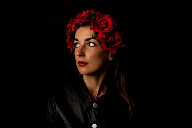 Pensive jeune femme en guirlande de fleurs rouges