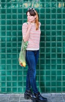 Pensive jeune fille de race blanche avec un sac en filet avec des légumes sur un mur vert dans la rue