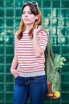 Pensive jeune fille de race blanche avec un sac en filet sur son épaule avec des légumes sur un mur vert dans la rue