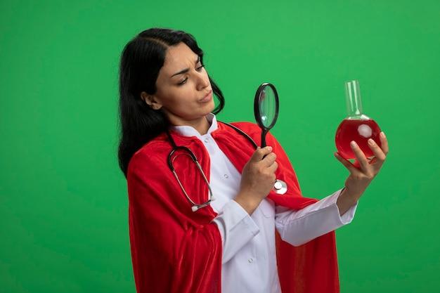 Pensive jeune fille de super-héros portant une robe médicale avec stéthoscope tenant et regardant la bouteille en verre de chimie remplie de liquide rouge avec loupe isolé sur vert