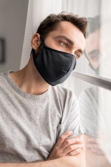 Pensive jeune homme au masque noir appuyé sur la fenêtre tout en contemplant la ville vide pendant la pandémie de coronavirus, temps du concept de distance sociale