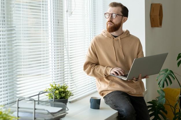 Pensive jeune homme barbu à capuche assis sur le rebord de la fenêtre et tenant un ordinateur portable tout en pensant à la conception