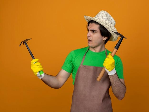 Pensive jeune jardinier mâle en uniforme portant chapeau de jardinage avec des gants tenant et regardant houe râteau avec râteau isolé sur orange