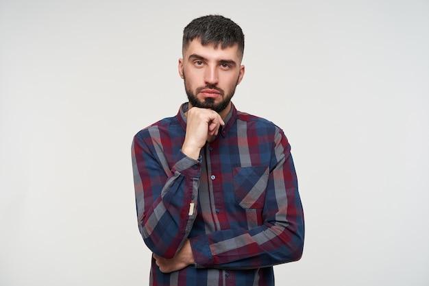Pensive jeune mec brune barbu aux yeux bruns s'appuyant son menton sur la main levée et faisant sourcil tout en regardant pensivement, debout sur un mur blanc