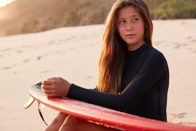 Pensive jolie jeune femme pense à la compétition de surf, étant profondément dans ses pensées